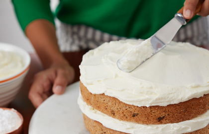 A spatula spreading creamy frosting on two-layered carrot cake