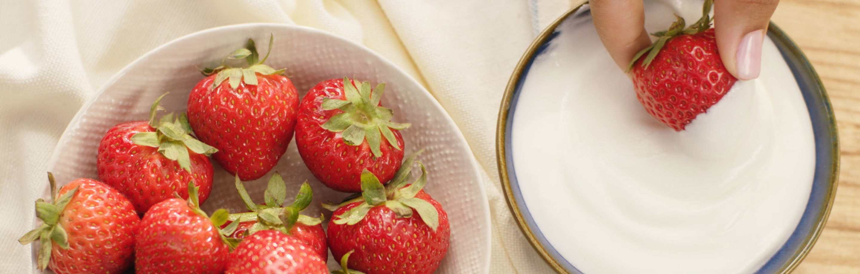 Bowl of strawberries next to cream cheese fruit dip