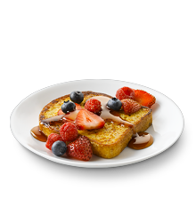 a plate of french toast with mixed berries and syrup