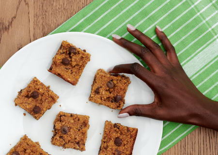 closeup of a hand reaching to grab a chickpea blondie bar from a plate