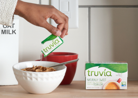 hand holding a Truvia packet and sprinkling its contents on a bowl of cereal