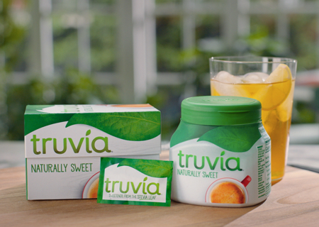 Truvia packets and spoonable jar posed next to a glass of lemonade