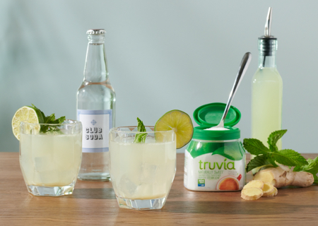 Ginger mojito mocktails sitting on a table with various ingredients and Truvia sweetener