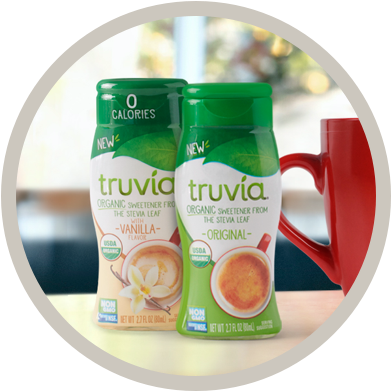 Two Truvia organic liquid sweetener bottles side by side next to a mug