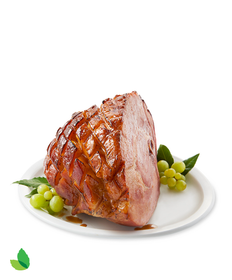 Unsliced glazed ham on a plate with green garnish