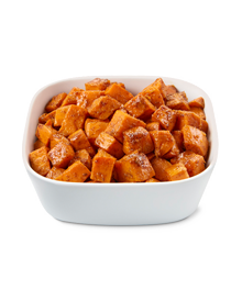 Bowl of golden browned candied yam cubes