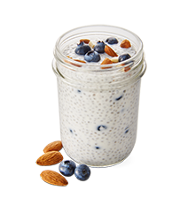 a jar with tapioca pudding and fresh berries and nuts