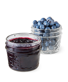 A jar of fresh blueberry jam in front of a jar of fresh blueberries