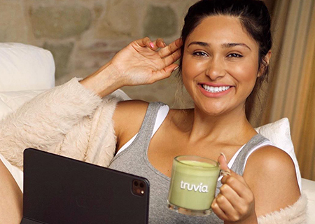 smiling young woman lounging on a couch with a laptop and a truvia mug full of green smoothie