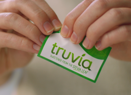 Hands opening a Truvia Sweetener Packet