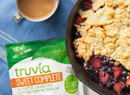Bag of Truvia Sweet Complete laying on table next to Berry Cobbler Skillet