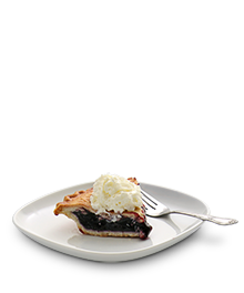 Slice of blueberry pie with a scoop of vanilla ice cream on a small white serving dish