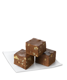 Three cubes of walnut fudge on parchment paper
