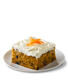 Slice of carrot cake with creamy white frosting on a small serving plate