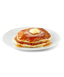 Stack of two fluffy pancakes with butter and syrup on a small white plate