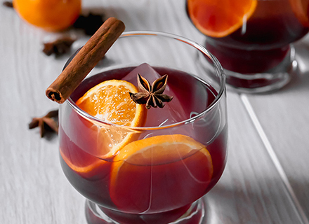 closeup of mulled wine cocktail with lemon slices and cinnamon sticks