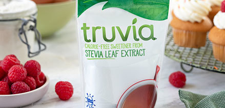 Truvia calorie-free pouch on table with raspberries and cupcakes